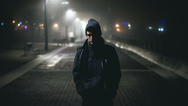 un uomo triste sulla strada nella notte