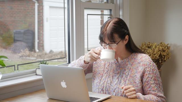 una cristiana guarda il computer bevendo un caffè